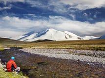 Man att sitta bara på flodbanken mot det snöig berget och b arkivbild