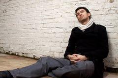 Man att sitta på golv med backen mot väggen Royaltyfri Fotografi