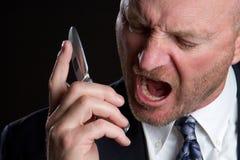man att skrika för telefon Arkivfoto