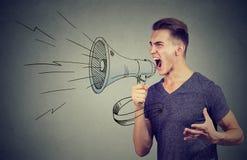 Man att skrika in i en megafon som gör ett meddelande arkivbild