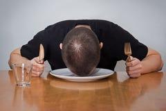 Man att sova huvudet på en platta som är trött av väntande på mat royaltyfria bilder
