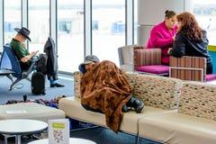 Man att sova i en flygplats under en filt Arkivbild