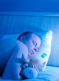 Man att sova i en omfamning med en mjuk leksak Fotografering för Bildbyråer