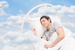 Man att sova på en säng i molnen arkivfoto