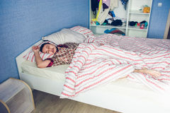 Man att sova på säng i form av ett hellångt Royaltyfri Foto