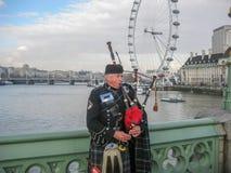 Man att spela den säckpipe- iklädda traditionella skotska dräkten på banker av flodThemsen arkivbild