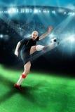 Man att spela fotboll och att skjuta en boll i leken Royaltyfri Bild