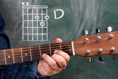 Man att spela gitarrackord som visas på en svart tavla, ackord D arkivbilder