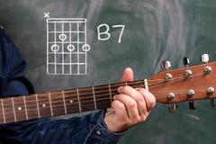 Man att spela gitarrackord som visas på en svart tavla, ackordet B7 arkivbilder
