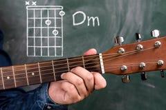 Man att spela gitarrackord som visas på en svart tavla, ackordet Dm arkivbild