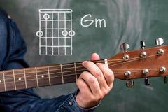Man att spela gitarrackord som visas på en svart tavla, ackordGm arkivbild