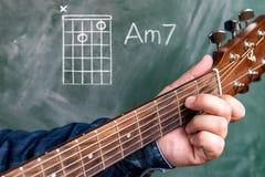 Man att spela gitarrackord som visas på en svart tavla, minderårig 7 för ackord A arkivbilder