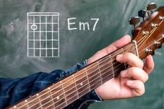 Man att spela gitarrackord som visas på en svart tavla, minderårig 7 för ackord A royaltyfri foto