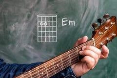 Man att spela gitarrackord som visas på en svart tavla, minderårig för ackord E arkivbilder