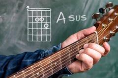 Man att spela gitarrackord som visas på en svart tavla, sus för ackord A arkivbilder