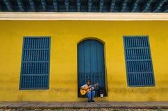 Man att spela gitarren framme av en av de koloniala byggnaderna Royaltyfria Foton