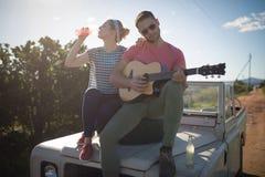Man att spela gitarren medan kvinnan som har en drink Arkivfoto