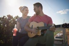 Man att spela gitarren medan kvinnan som har en drink Royaltyfri Fotografi