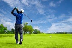 Man att spela golf på en golfbana i solen, golfare slår den svepande golfbanan i sommaren arkivbild