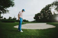 Man att spela golf på en solig dag på en härlig golfbana Arkivfoto