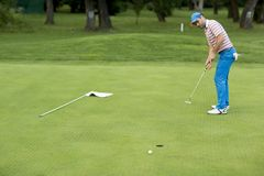 Man att spela golf på en solig dag på en härlig golfbana Arkivbild