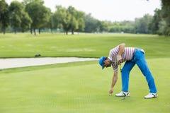 Man att spela golf på en solig dag på en härlig golfbana Fotografering för Bildbyråer