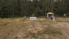 _ Man att spela ilskna fåglar för verkliga livet med den jätte- katapulten på kanten av skogen stock video