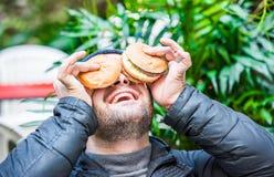 Man att spela med hans mat - att förlägga hans hamburgare på hans framsida fotografering för bildbyråer