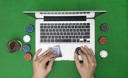 Man att spela online-poker med bärbara datorn på en grön tabell med chiper Arkivbild