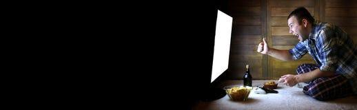 Man att spela på en konsol på styrspaken för den stora TVstenrans royaltyfri bild