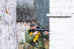 Man att spela paintball i overaller med ett vapen Fotografering för Bildbyråer