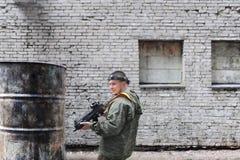 Man att spela paintball i overaller med ett vapen på den kastade fabriken Arkivbilder