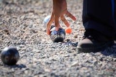 Man att spela petanque, bollar på jordningen Royaltyfria Bilder