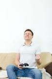 Man att spela videospel med joypad eller styrspaken för att trösta eller PC:n Royaltyfri Foto
