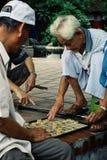 man att spela xiangqi schackleken för traditionell kines på en fyrkant arkivfoton