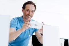Man att stråla, medan spela med mobiltelefonen på lagret Royaltyfri Fotografi