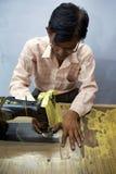 Man att sy flera stycken av kläder i Agra för Pushpanjali Arkivfoto