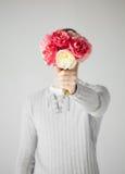 Man att täcka hans framsida med buketten av blommor Arkivbild