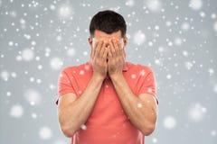 Man att täcka hans framsida med händer över snö Royaltyfri Fotografi