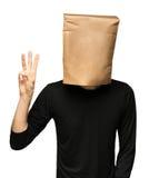man att täcka hans huvud genom att använda en pappers- påse tre Arkivfoto