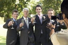 Man att ta en bild av fem män som rostar med vinexponeringsglas på brölloppartiet royaltyfri foto