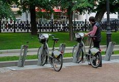 Man att ta en cykel för hyra i Moskva Royaltyfria Bilder