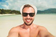 Man att ta en selfie på stranden, medan bära skuggor och hatten Arkivbild