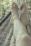 Man att ta en ta sig en tupplur på en hängmatta på naturen Royaltyfri Foto