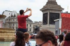 Man att ta ett foto på Kanada dagberömmar i London ` s Trafalgar Square 2017 Arkivfoton