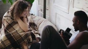 Man att ta foto av kvinnan på flyttning-film kamera Ung flicka till skinn under en filt som poserar till fotografen stock video