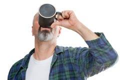 Man att ta ner den sista droppen av kaffe arkivbild