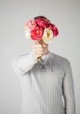 Man att täcka hans framsida med buketten av blommor Arkivbilder