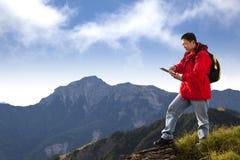 Man att trycka på tabletPCen på berg royaltyfri fotografi