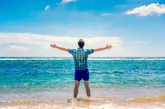 Man att tycka om frihet i vatten på stranden Arkivbilder